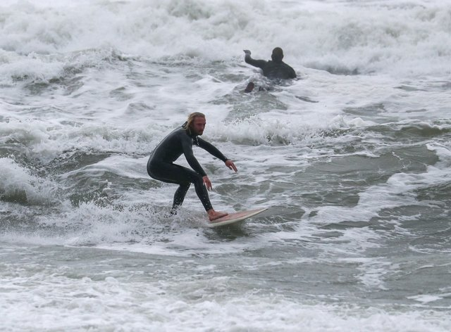 People surfing in the sea off Boscombe beach in Dorset