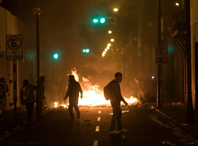Protesters walks towards a barricade in Lima, Peru
