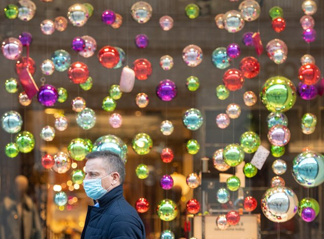 Masked man passing Christmas display