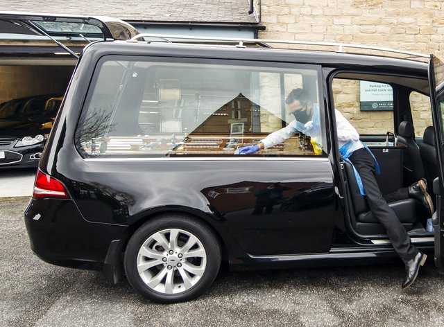 Funeral director Andrew Atkins wears PPE as he disinfects a hearse at Full Circle Funerals