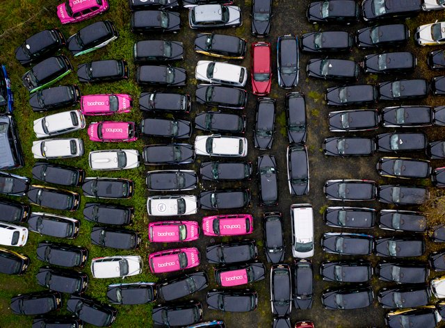 <p>Fields dotted around the edge of London are being used to store unwanted taxis</p>