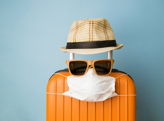 Travel restriction abstract made of tourist in form of of luggage with face mask, sunglasses and hat (iStock/PA)