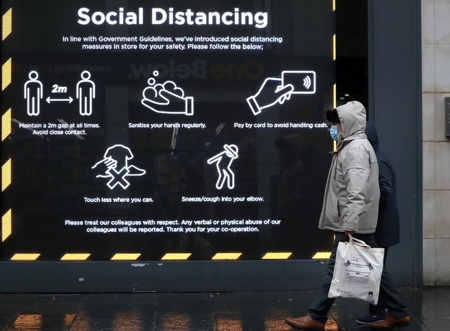 A member of the public walks past a social distancing sign