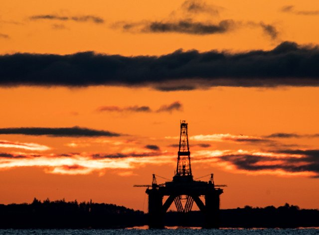 The sun rises behind a redundant oil platform