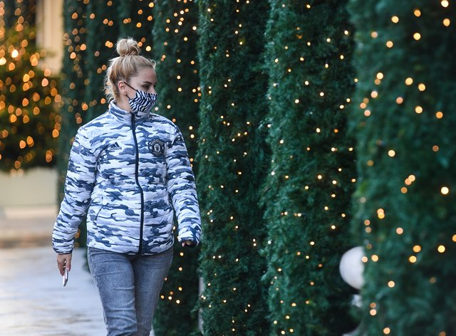 A woman wearing a face mask passes Christmas lights outside shops on Oxford Street in London