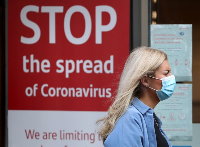 Woman with mask in front of coronavirus sign
