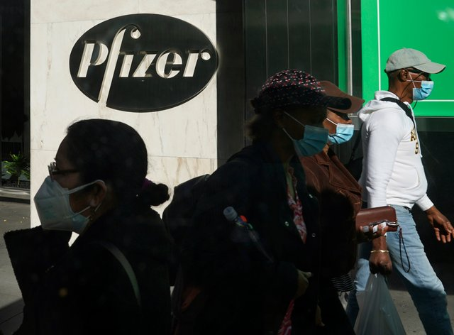 Masked pedestrians walk past Pfizer's world headquarters in New York