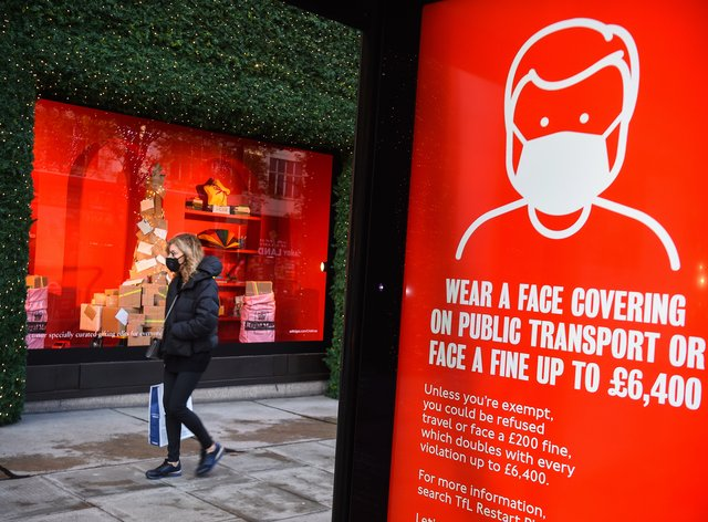 A woman wearing a face mask passes a screen advising the wearing of face masks on Ox