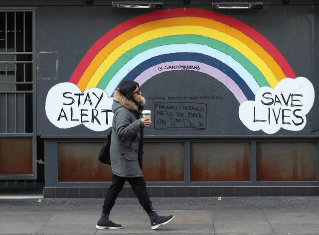 A person walks past a rainbow mural on a closed bar in Soho, London (Yui Mok/PA)
