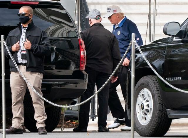 Donald Trump walks to a motorcade