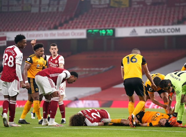 Players react after Arsenal's David Luiz (left, floor) clashes heads with Wolves striker Raul Jimenez (right, floor) at Emirates Stadium