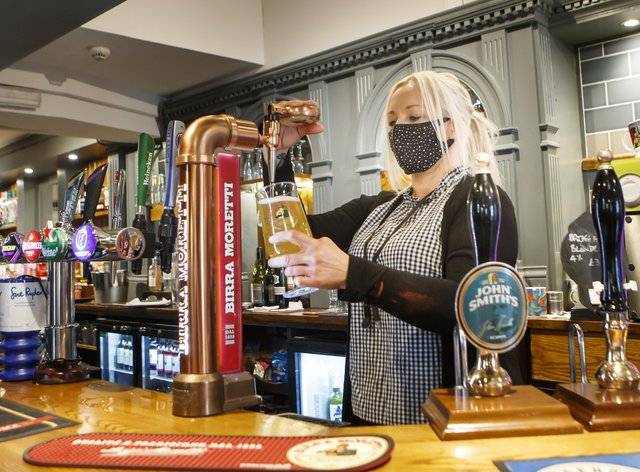 A barmaid pulls a pint