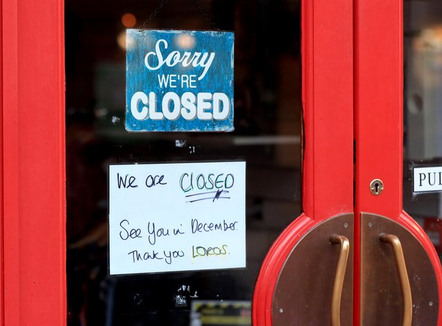 A 'Sorry We're Closed' sign on a shop door