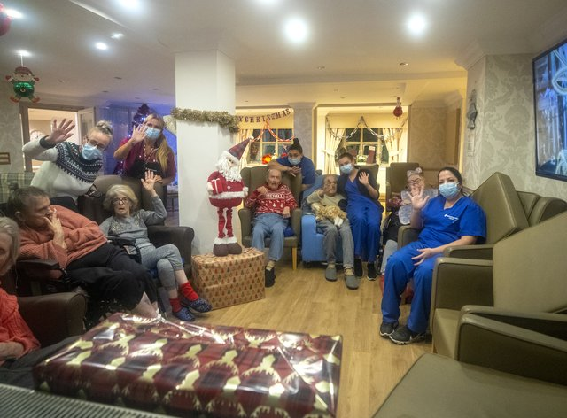 Residents and care workers at Churchview Nursing Home in Liverpool watch a video of the city's Christmas lights switch-on