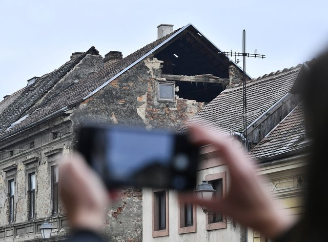 A resident takes a photograph of the damage caused by an earthquake in Sisak, Croatia