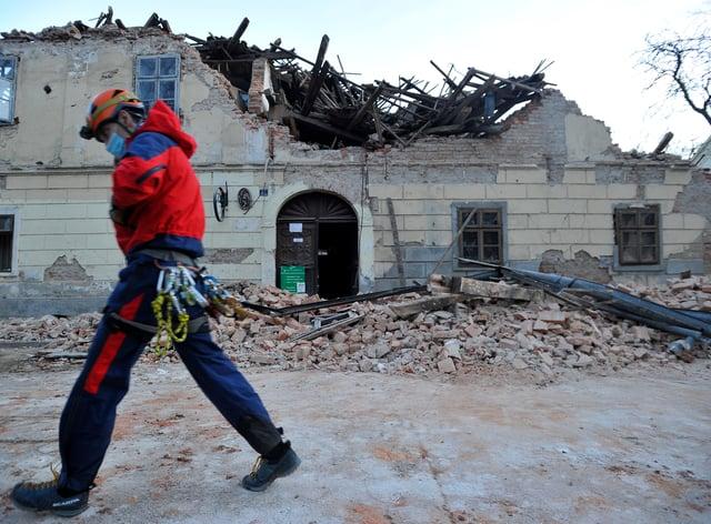 A rescuer walks past a building damaged in an earthquake in Petrinja, Croatia