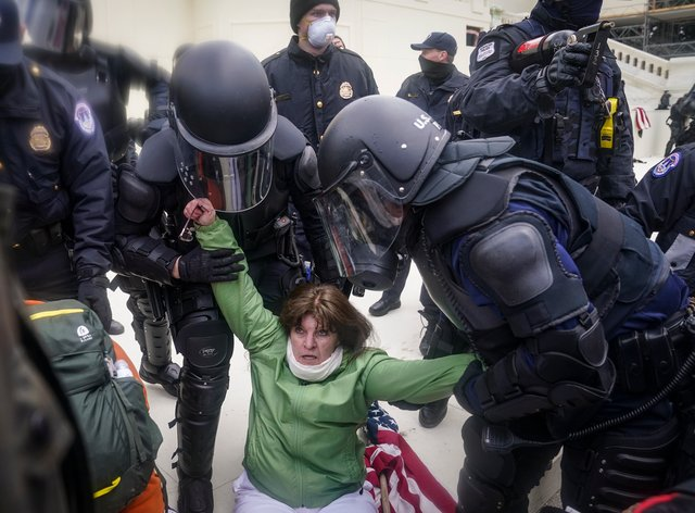 Police help woman up during Washington riot