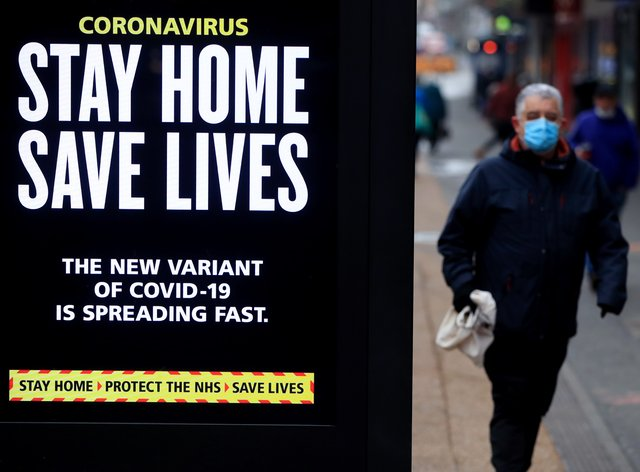 People pass a Stay Home, Save Lives electronic board
