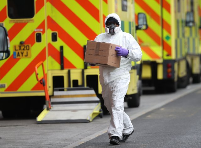 A man wearing PPE makes a delivery to the Royal London Hospital