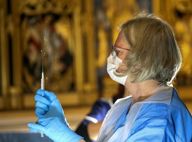 The Pfizer coronavirus vaccine is prepared by a health worker
