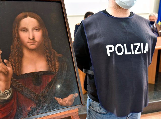 An Italian police officer stands by a copy of the Salvator Mundi in Naples