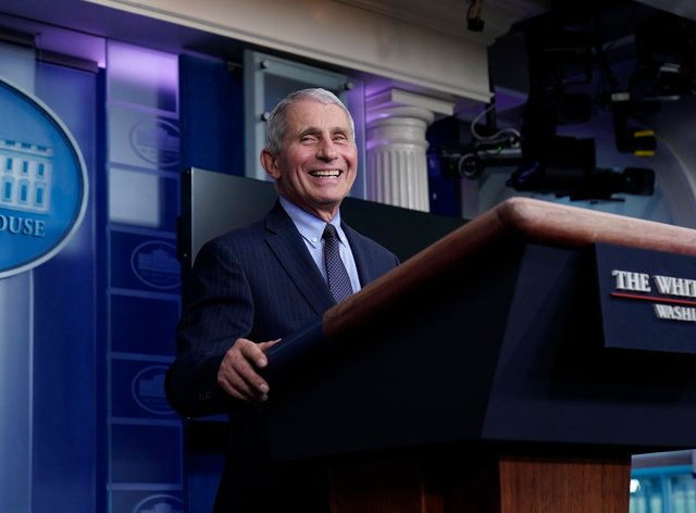 Dr Anthony Fauci laughs while speaking in the press room at the White House