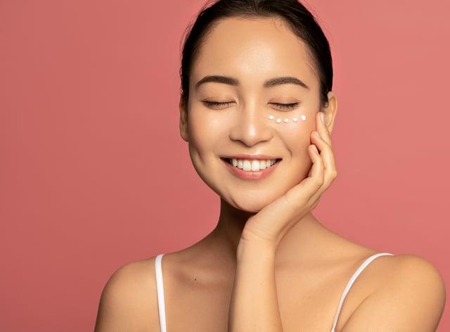 woman with eyes closed applying eye cream under eyes