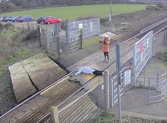 A woman lying down on railway tracks to pose for photographs in East Sussex