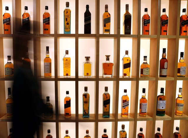 A person walks past Diageo-owned whiskies on the whisky wall at its headquarters in Edinburgh