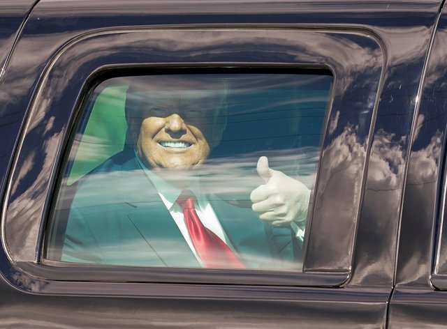 President Donald Trump gestures to supporters from inside a vehicle