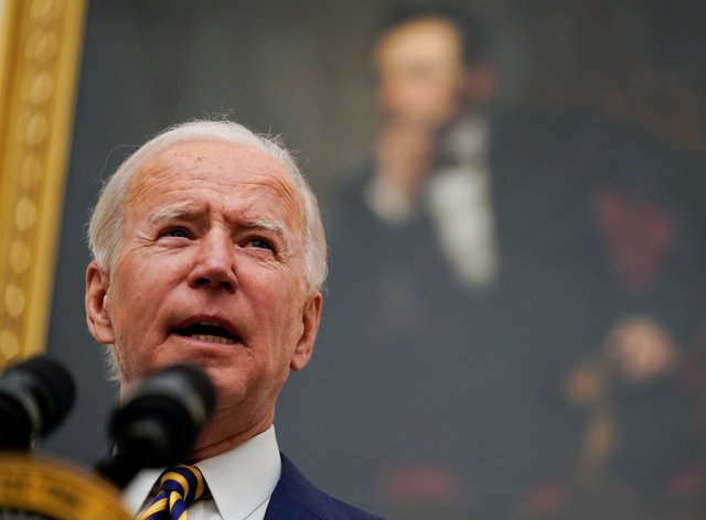 President Joe Biden speaks into a microphone