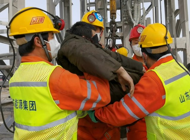 Rescuers carry a miner who was trapped in a gold mine in Qixia City in east China's Shandong Province