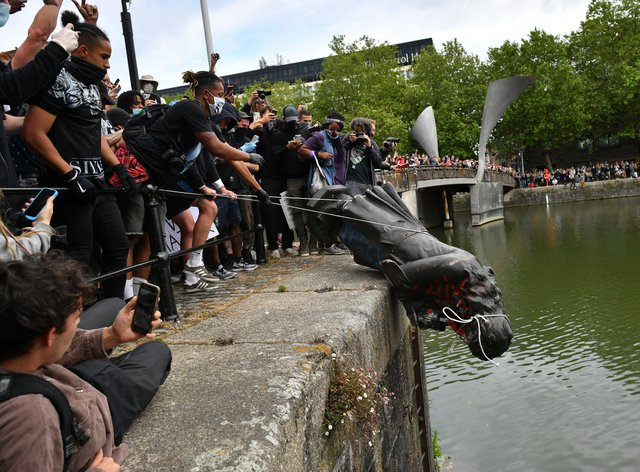 A statue was toppled before being thrown into a harbour