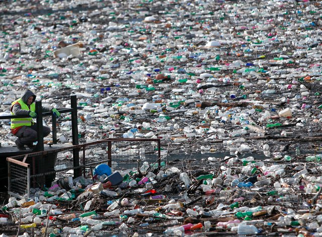 A boat pushes rubbish stuck at the foot of a hydropower plant in Serbia