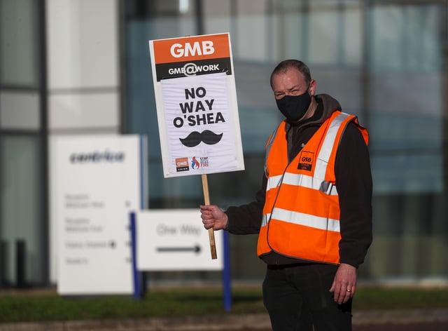 A GMB union member holds a strike placard