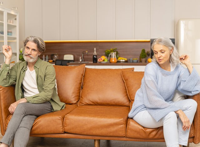 Unhappy married couple sitting at opposite ends of a sofa