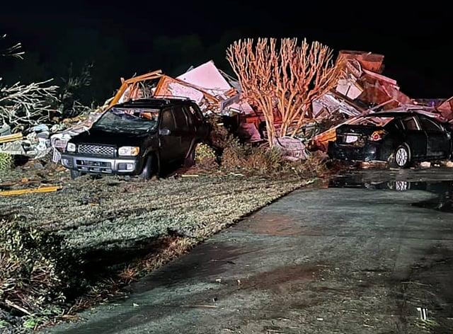 Damaged vehicles sit among debris after a deadly tornado tore through Brunswick County, North Carolina