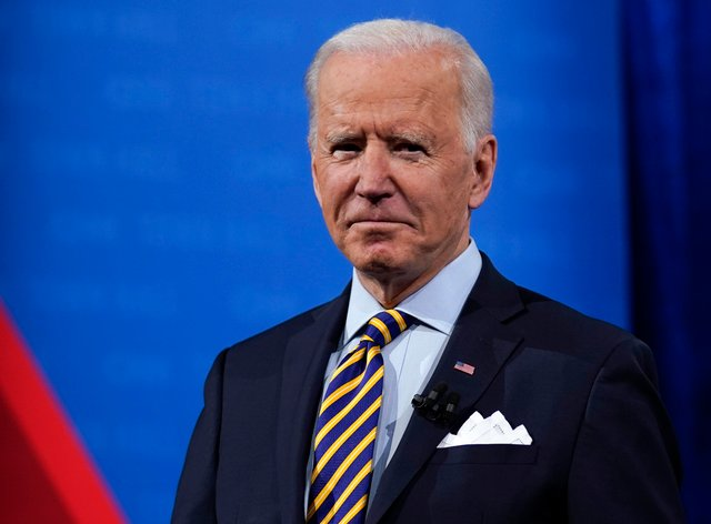 President Joe Biden stands on stage during a break in a televised town hall event