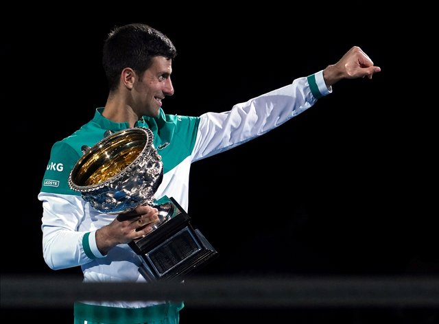 Novak Djokovic holds the Norman Brookes Challenge Cup for a ninth time