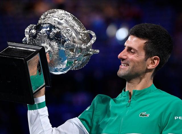 Novak Djokovic holds the Norman Brookes Challenge Cup aloft