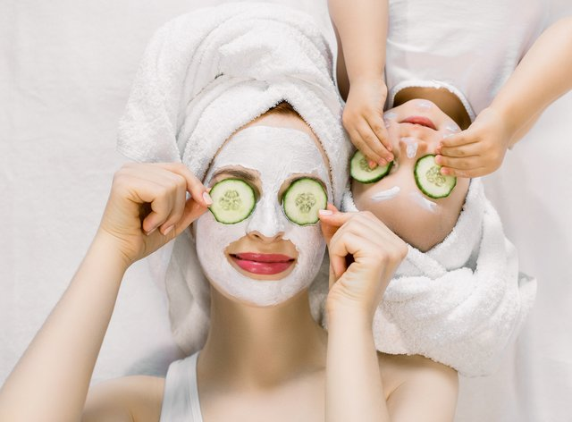 mother and daughter with facial masks on and cucumbers on their eyes