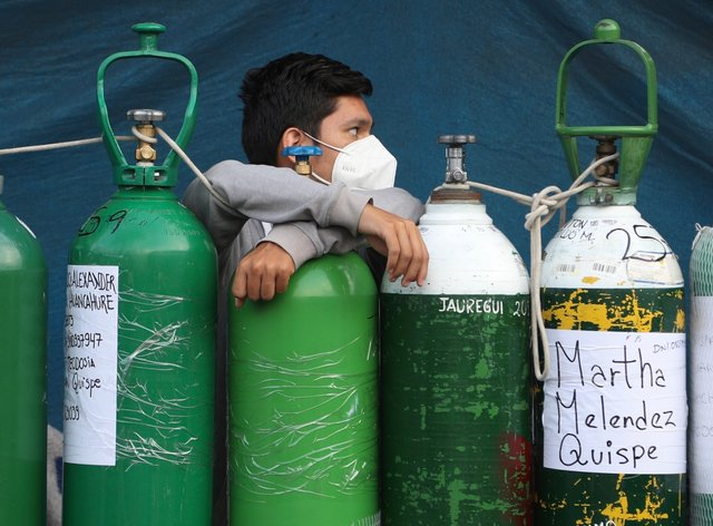 A youth rests on his empty oxygen cylinder waiting for a refill shop to open in Lima, Peru