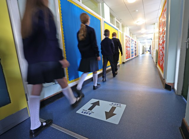 Pupils walk through school corridor