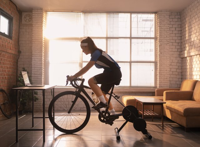 Woman riding an exercise bike in the living room (