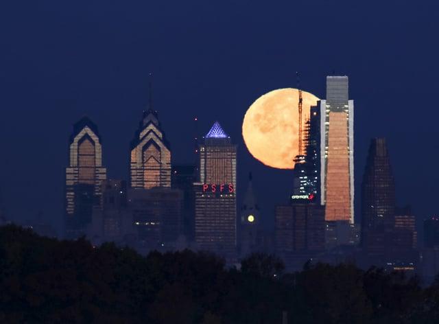A supermoon sets behind the Philadelphia skyline (Joseph Kaczmarek/AP)