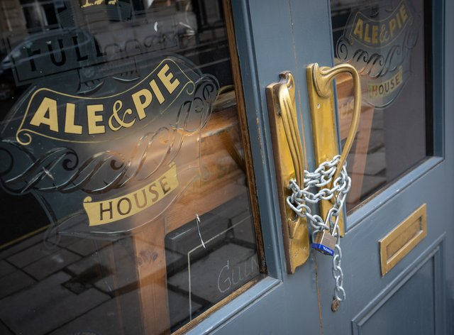 Chains secure the doors of a closed Fuller's pub in London