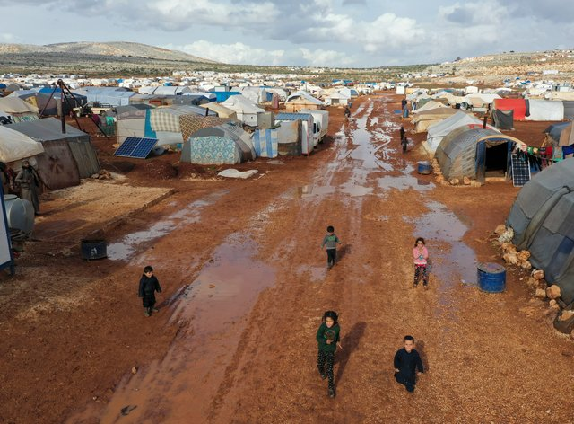 Syrian refugees walk through a camp for displaced muddied by recent rains near the village of Kafr Aruq, in Idlib province, Syria (Ghaith Alsayed/AP)