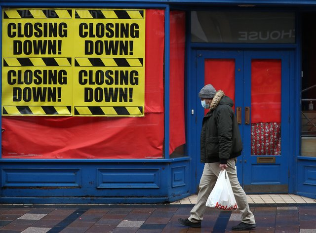 A man walks past a shop with 'Closing down' signs