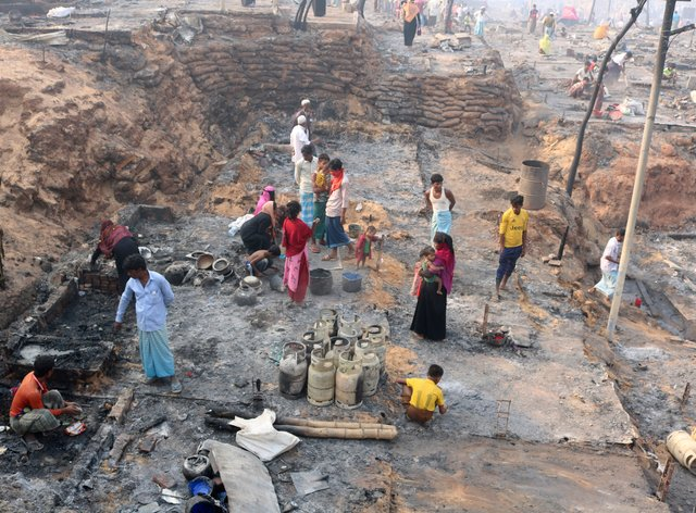 Rohingya refugees stand at the site of the fire