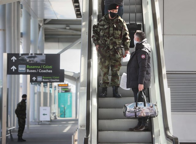 A passenger is escorted to a coach by a member of the defence forces after arriving at Dublin Airport